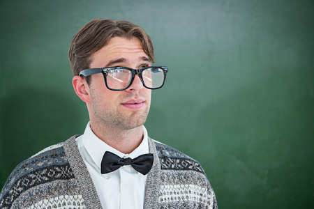 geeky: Thoughtful geeky hipster  against green chalkboard