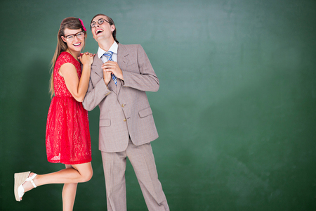 together with long tie: Hipster couple having fun together  against green chalkboard
