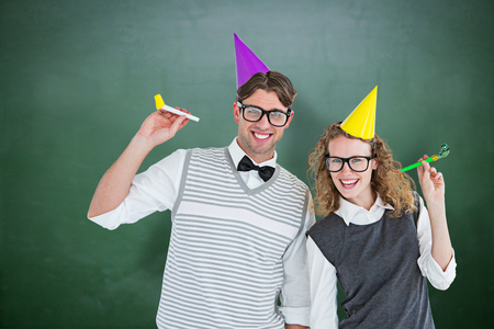 cheesy grin: Geeky couple with party hat and party horn against green chalkboard