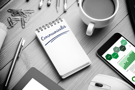 communicates: The word communicates and business graphs against notepad on desk