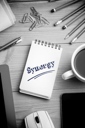 sinergia: La palabra sinergia contra el bloc de notas en el escritorio