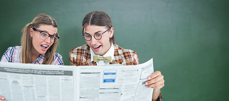 together with long tie: Geeky hipsters reading the newspaper against green chalkboard