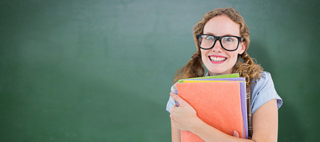 cheesy grin: Geeky hipster woman holding files  against green chalkboard Stock Photo