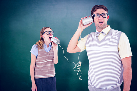 tin can phone: Geeky hipster couple speaking with tin can phone  against green chalkboard Stock Photo