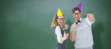 cheesy grin: Happy geeky hispser couple dancing with party hat against green chalkboard