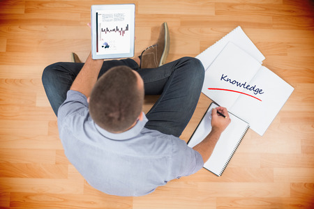 knowledge business: The word knowledge and business graphs against young creative businessman looking at tablet Stock Photo