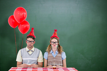 geeky: Geeky hipster couple celebrating his birthday  against green chalkboard