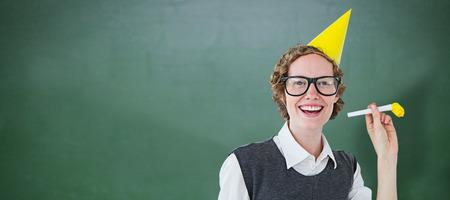 Geeky hipster in feestmuts met hoorn tegen groene krijtbord