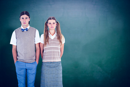 couples people: Unsmiling geeky hipsters looking at camera  against green chalkboard Stock Photo
