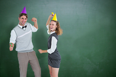 cheesy grin: Geeky couple dancing with party hat  against green chalkboard