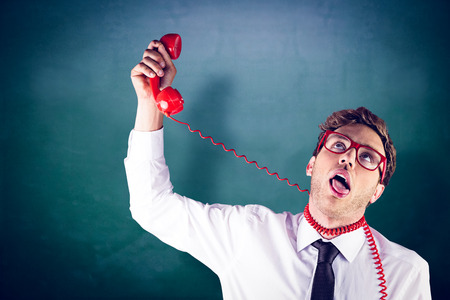 strangling: Geeky businessman strangling himself with telephone against green chalkboard Stock Photo