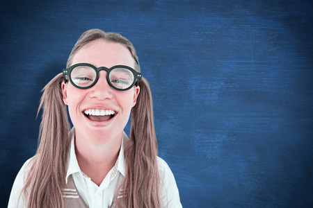 cheesy grin: Female geeky hipster smiling at camera against blue chalkboard