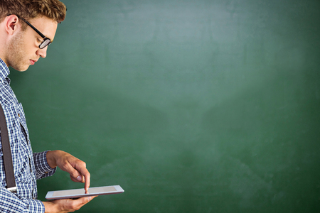 Geeky businessman using his tablet pc against green chalkboard