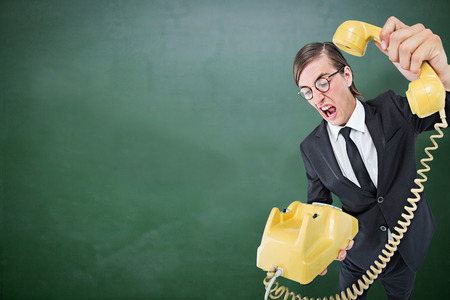 hanging up: Geeky businessman shouting and hanging up the telephone against green chalkboard
