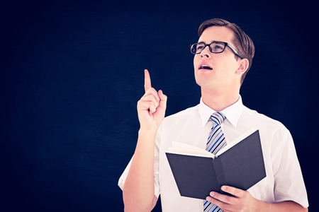geeky: Geeky businessman reading from book against blackboard