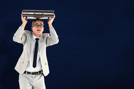 sheltering: Handsome businessman sheltering with briefcase against navy blue