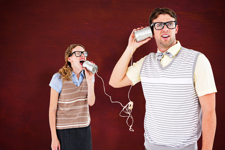 tin can phone: Geeky hipster couple speaking with tin can phone  against desk