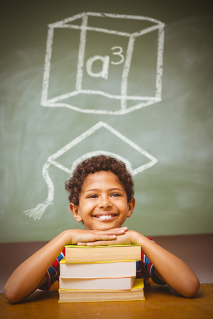 cubed: A cubed against little boy with stack of books in classroom Stock Photo