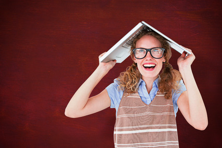 table skirt: Geeky hipster woman covering her head with her laptop  against desk Stock Photo