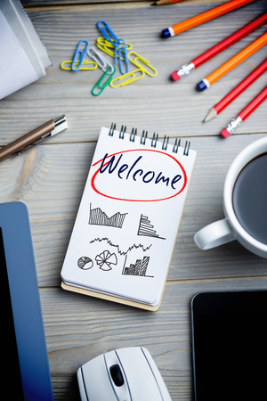 welcome desk: The word welcome and business graphs against notepad on desk