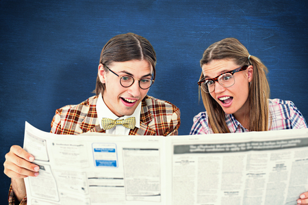 together with long tie: Geeky hipsters reading the newspaper against blue chalkboard