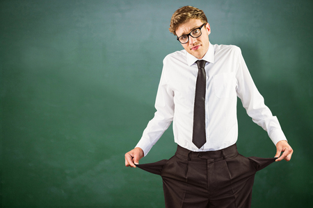 pocket: Geeky businessman showing his empty pockets against green chalkboard