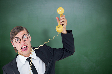 phone cord: Geeky businessman being strangled by phone cord  against green chalkboard Stock Photo