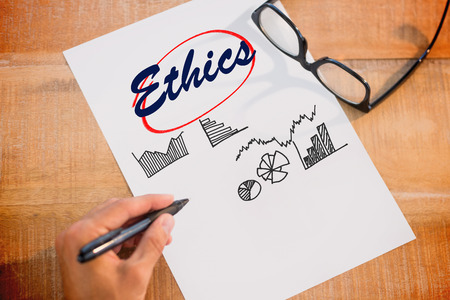 morals: The word ethics and left hand writing on white page on working desk against business graphs Stock Photo