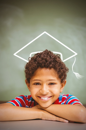 multiracial: Graduation hat vector against little boy smiling in classroom Stock Photo