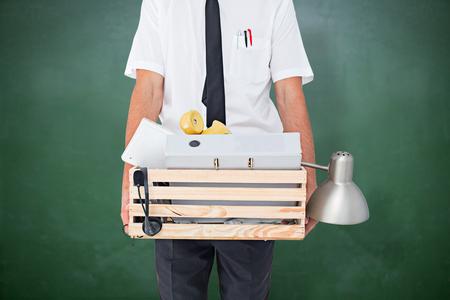 belongings: Fired businessman holding box of belongings  against green chalkboard