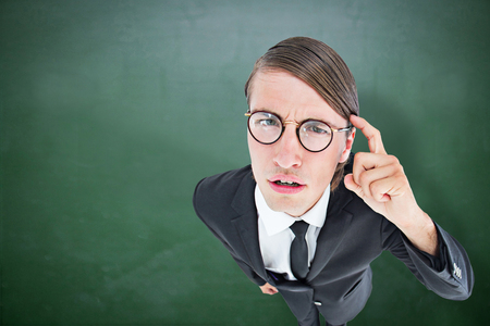 geeky: Thoughtful geeky businessman against green chalkboard Stock Photo