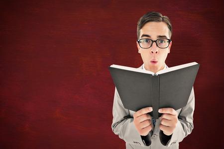 preacher: Geeky preacher reading from black bible against desk Stock Photo