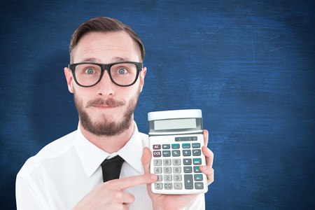 cheesy grin: Geeky businessman pointing to calculator  against blue chalkboard
