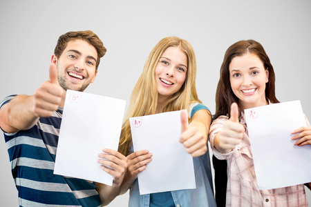 Students holding up exam and doing thumbs up against grey vignette Stok Fotoğraf - 44597990