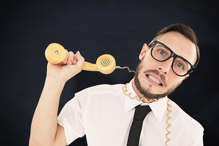 phone cord: Geeky businessman being strangled by phone cord against blackboard