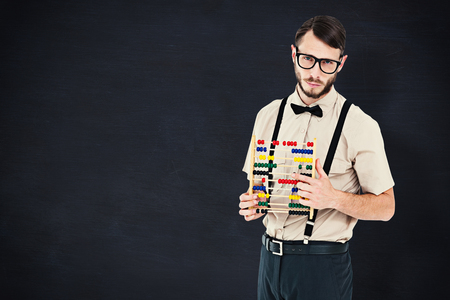 geeky: Geeky hipster holding an abacus against blackboard