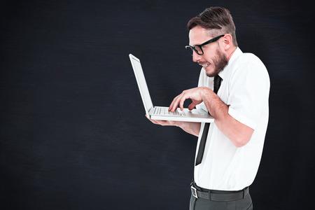 geeky: Geeky businessman using his laptop against blackboard