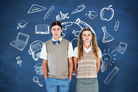 unsmiling: Unsmiling geeky hipsters looking at camera  against blue chalkboard Stock Photo