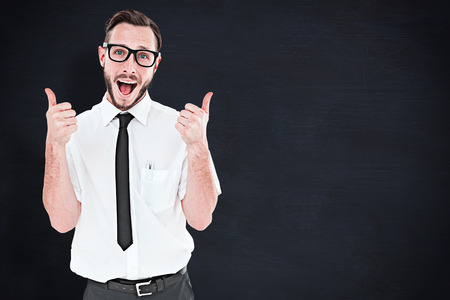 Geeky young man showing thumbs up against blackboard