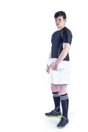 pelota rugby: Retrato de un jugador de rugby sosteniendo una pelota de rugby en un fondo blanco