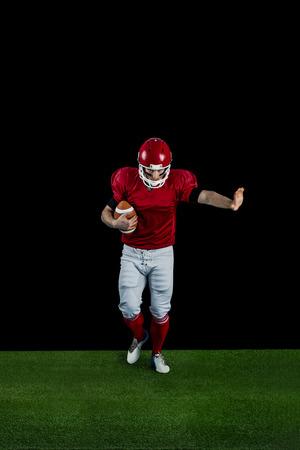 wrestle: American football player wrestling through and protecting football on american football field