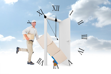 against the clock: Happy delivery man with trolley of boxes running on white background against clock counting down to midnight Stock Photo