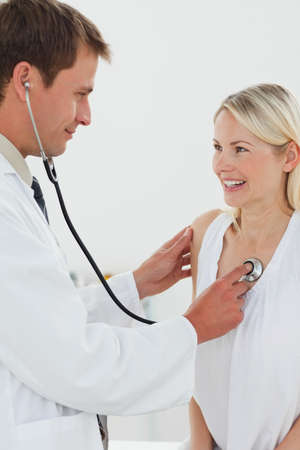 beat: Smiling male doctor checking his patients heart beat