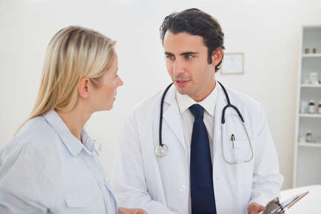 examination room: Doctor talking with his female patient in his examination room