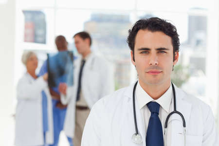 black professional: Young doctor with three colleagues behind him