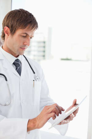 one mid adult male: Serious doctor using his tablet pc in front of a window
