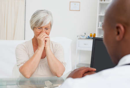 hoping: Mature woman hoping for good news from her doctor