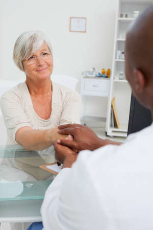 reassurance: Doctor holding mature female patients hand