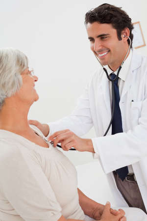 heart beat: Smiling young doctor measuring mature patients heart beat