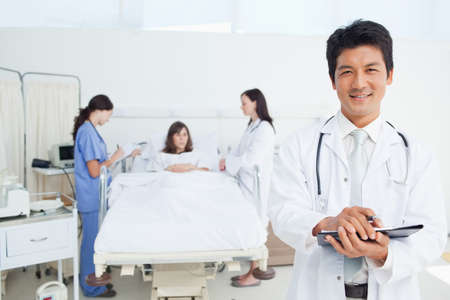 treating: Doctor smiling as he holds a clipboard while a nurse and a doctor are treating a patient in the background